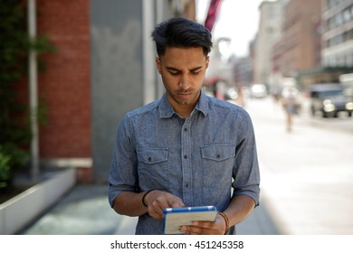Young southeast Asian man in New York City using tablet computer