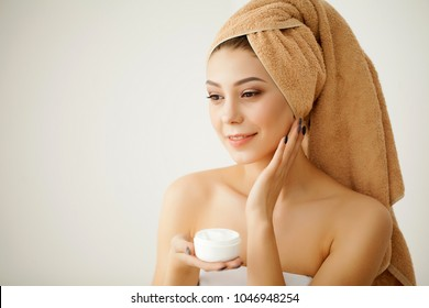 Young Spa Model with Clear Skin and Towel. Beautiful Spa Woman Applyng Monsturizing Cream. Skincare, Bodycare and Spa Beauty Concept
