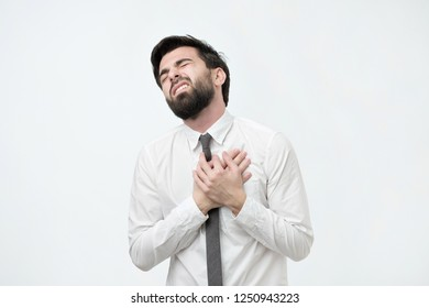 Young spanish bearded man having heart attack on white background. Having health problem because of hard working lifestyle.