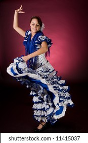 Young Spanish flamenco dancer in a blue dress, in full motion
