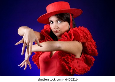 Young Spanish flamenco dancer performing with a red hat