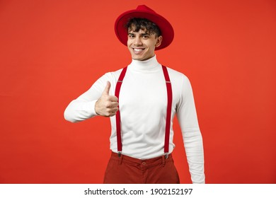Young spanish latinos smiling happy gladden stylish fashionable student man 20s in casual hat white shirt trousers with suspenders show thumb up like gesture isolated on red background studio portrait