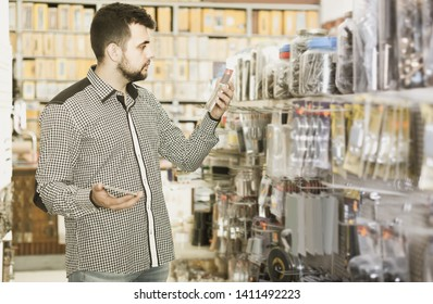 Young spanish man deciding on best DIY details in houseware store