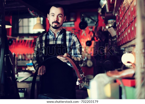 Young spanish man worker displaying various belts in leather workshop
