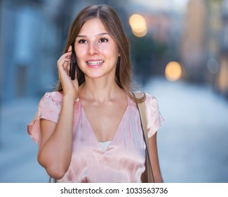 young spanish woman looking to  phone in hands and chatting in city