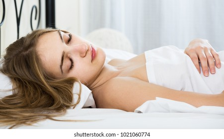 Young spanish woman lying in bed under sheet with closed eyes