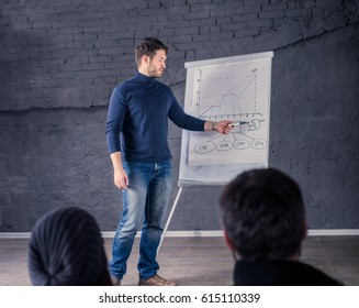 Young speaker man talking to audience during conference. He is giving a lecture and showing graph on flipchart.  Business presentation concept