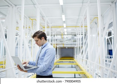 Young specialist with laptop browsing in the net during work in mining farm