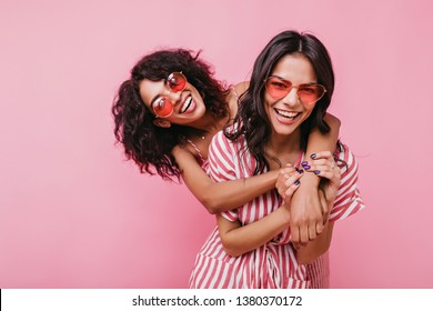 Young, spectacular models vigorously pose for portrait in studio. Tanned sisters embrace and laugh in unusual glasses