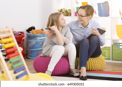 Young speech therapist working with child in colorful educational playroom