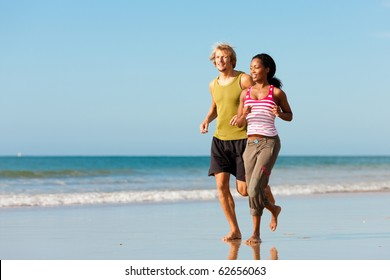 Young sport couple - Caucasian man and African-American woman - jogging on the beach