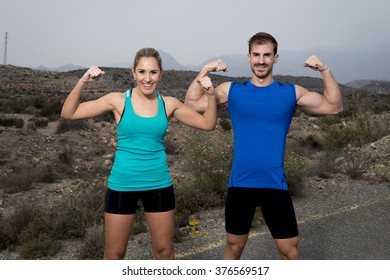 young sport couple posing and showing arms biceps muscles smiling happy girl wearing cyan tank top and man blue singlet both with folded arms in fitness club advertising style