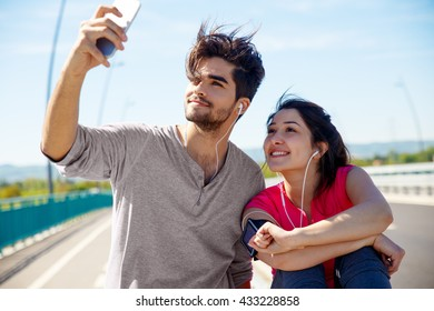 Young sport couple resting after jogging, They are taking selfie.