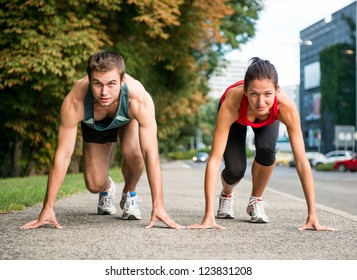 Young sport couple in starting position prepared to compete and run