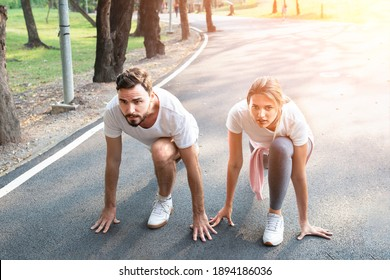 Young sport couple in starting position prepared to compete, Look forward. Fitness couple ready for running race on an outdoor park. challenging in powerful confident starting line pose.
