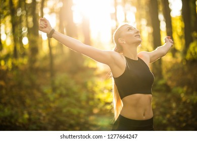 Young sport fit woman with raised hands after run in park on sunset