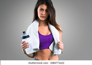 Young sport girl with a bottle and towel on grey background