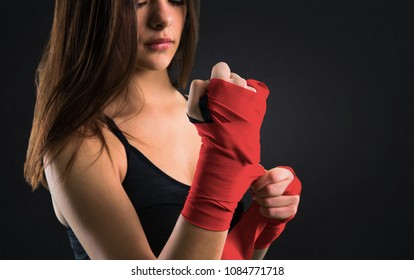 Young sport girl in boxing bandages on black background