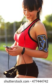 Young sport girl checking workout on smart watch in the street.Woman looking at the smart watch and smile