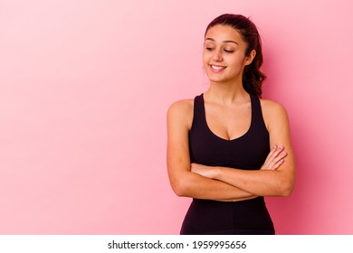 Young sport Indian woman isolated on pink background smiling confident with crossed arms.