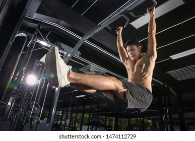 Young sport man doing exercises on horizontal bar in a gym club.