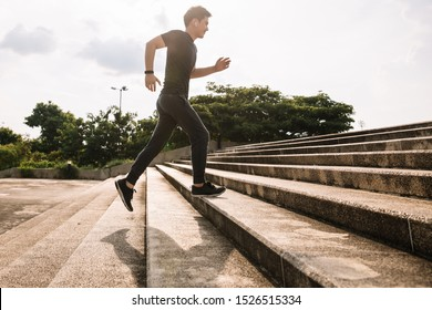 Young sport man running upstairs on city stairs