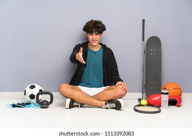 Young sport man sitting on the floor around many sport elements handshaking after good deal