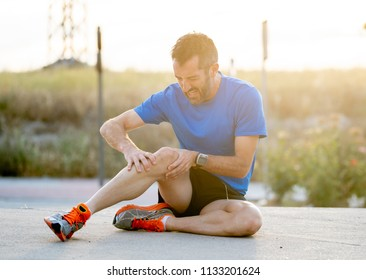 young sport man with strong athletic legs holding knee with his hands in pain after suffering muscle injury during a running workout training in asphalt road in muscular or ligament injury concept.
