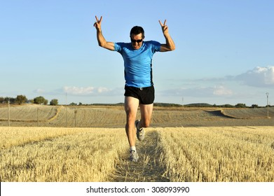 young sport man with sunglasses running outdoors on straw field ground in frontal perspective towards camera doing victory sign with arms and hands  in healthy lifestyle and competition concept