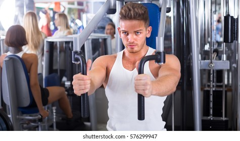 Young sport man training upper body using fly machine in gym