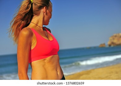 Young sport style woman standing on beach after workout