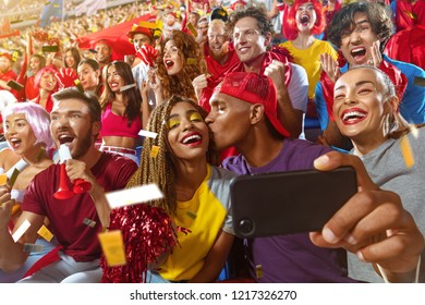 Young sport supporter happy fans at stadium. Beautiful black man and black woman support the football team during the match and making selfie photo