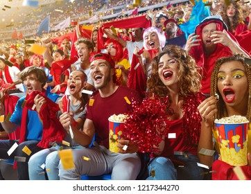 Young sport supporter happy fans cheering at stadium. Group of young woman and man with popcorn support the football team during the match