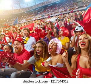 Young sport supporter happy fans cheering at stadium. Group of young woman and man support the football team during the match