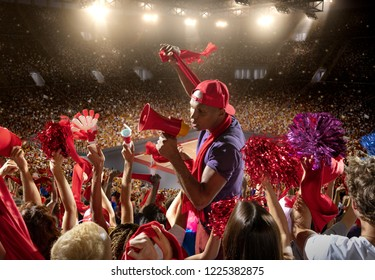 Young sport supporter happy fans at basketball arena. Beautiful black man support the basketball team during the game and shouting into a red mouthpiece