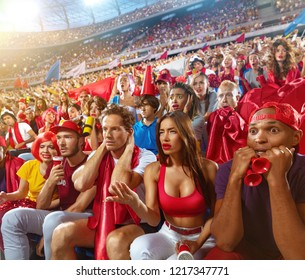 Young sport supporter sad fans at stadium. Group of young woman and man upset over losing football team during the match