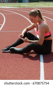 Young sport woman athlete sit and listen music on stadium before training
