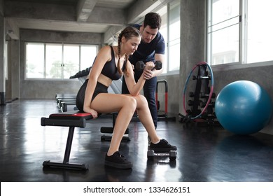 young sport woman exercise lifting dumbbells on the bench in fitness gym healthy .Muscular girl in sportswear training biceps  with personal trainer man workout.bodybuilding