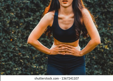 Young sport woman having pain at her stomach. Health problem concept.