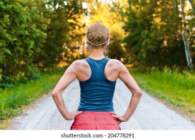 Young sport woman with muscular back stays on the road in the forest