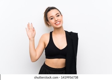 Young sport woman over white wall saluting with hand with happy expression
