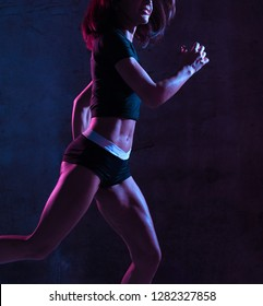 Young sport woman running jogging in gyn in blue and pink neon light on dark wall background