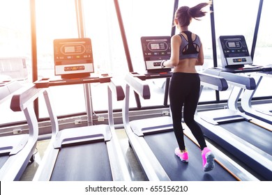 Young sport woman running on electric treadmill in gym at sunrise in the morning.