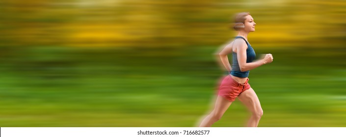 Young sport woman runs through forest very fast. Motion blur on background.