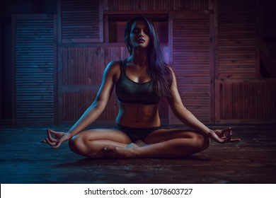 Young sport woman sitting in yoga meditation pose. Dark blue and pink night light.