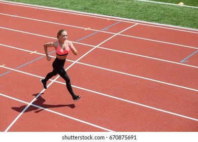 Young sport woman sprinter athlete running on stadium track