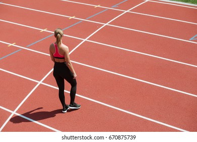Young sport woman sprinter athlete stand on stadium track