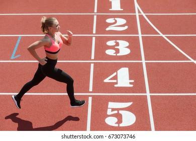 Young sport woman sprinter athlete running on stadium track