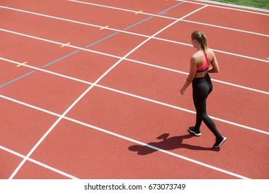 Young sport woman sprinter athlete go on stadium track