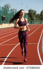 Young sport woman sprinter athlete jogging on stadium track, healthy lifestyle concept
